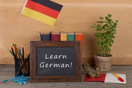 "Learning languages concept - blackboard with text ""Learn German"", flag of the Germany, books, chancellery"