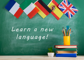 "flags of Spain, France, Great Britain and other countries, blackboard with text ""Learn a new language!"", books and chancellery"