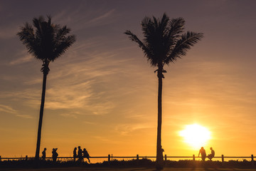 silhouette of tourists, locals and friends enyoing sunset with a drink on the beach in Broome, Western Australia