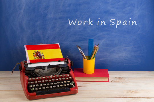"""work abroad concept - red typewriter, flag of Spain, books on table and blackboard with text """"Work in Spain"""""""