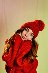 Close up face portrait of toothy smiling young woman wearing red sweater with red knitted cap.