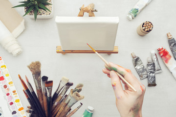 Painter holding a paintbrush in his hand. Canvas on the easel and artistic equipment on desk. Top view.