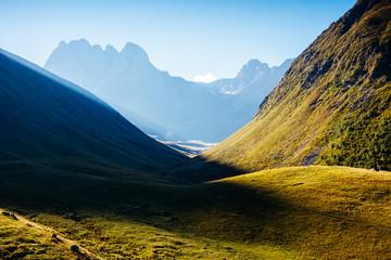Captivating scene of the alpine valley in sunlight. Main Caucasus ridge.