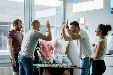 Fototapeta happy managers playing table football at office and having fun together