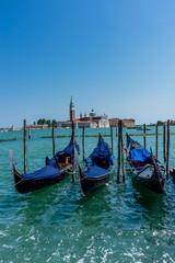 Gondolas moored by Saint Mark square with San Giorgio di Maggiore church in the background in Venice, Italy