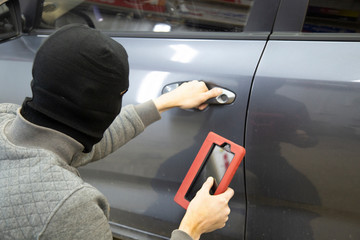 The hijacker tries to break into the car with a scanner. Code grabber . Car thief, car theft. - fototapety na wymiar