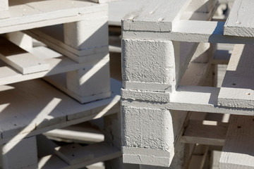 Stack of white painted wooden pallets