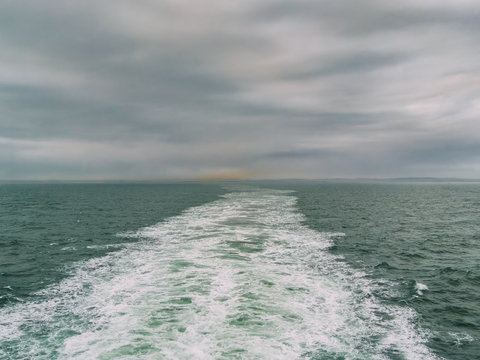 View from the back of a ferry crossing the English Channel, UK, Europe. Industrial/urban pollution from Portsmouth in the distance.