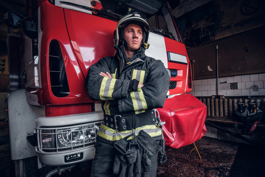 Portrait of a brave young fireman wearing protective uniform standing next to a fire engine in a garage of a fire department