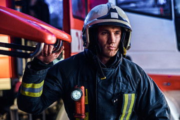 Portrait of a handsome fireman wearing a protective uniform with flashlight included standing in a fire station garage and looking sideways