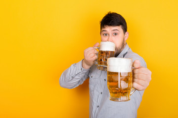 man drinks beer and offers the viewer a glass of beer, image on a yellow background