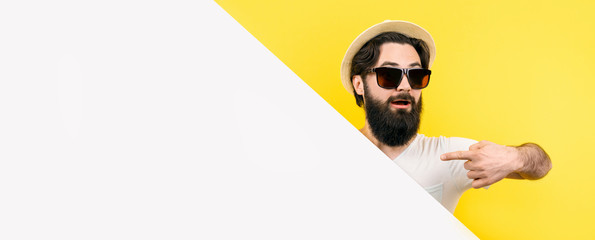 studio portrait of a bearded guy in sunglasses and hat, looking out from behind the empty banner and pointing at him, image on yellow background, summer holiday concept
