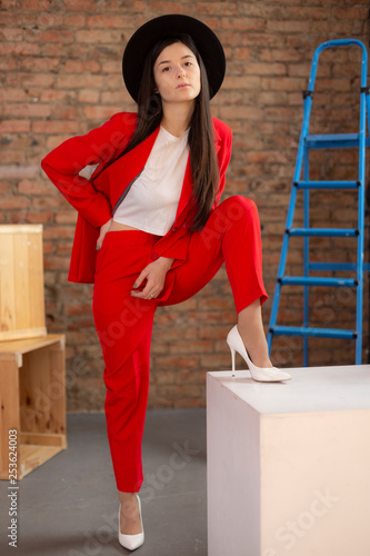 8ba1c7683 Wonderful girl model poses for a photo in bright red clothes adn hat in a  photo studio.The concept of shopping woman wear showroom.