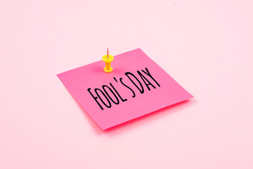 April Fools' Day text celebration background with paper sticky note and office pin on pink background. All Fools' Day, humor, prank, joke concept