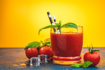Red cocktail with tomato juice between tomatoes, fresh basil and ice