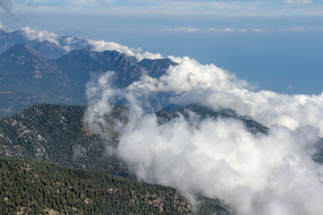Aerial view of clouds formation on sunny day over the mountain