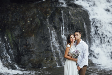 Wedding Beautiful couple sexy Bride dress young girl Brutal groom. Stylish man in costume on the nature landscape background. waterfall wedding river curren.