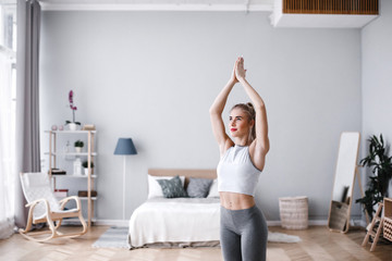 Young attractive woman practicing yoga, working out, wearing sportswear. Wall mural