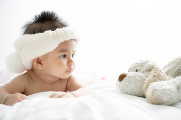 Happy Asian baby girl lying with dog doll on white bed sheets.