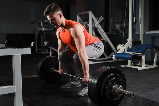Strong handsome fit man exercising in the gym. Personal trainer workout. Athletic man working out his muscles at deadlift. Fitness, healhty lifestyle, bodybuilding concept.