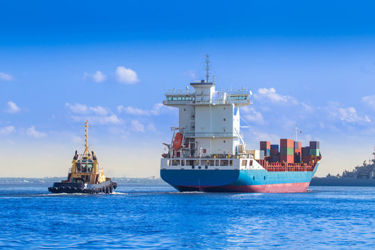 Cargo Ship. The ship carries cargo. Container ship. The tug boat navigates through the fairway. Maritime supply routes. Fairway in the port.