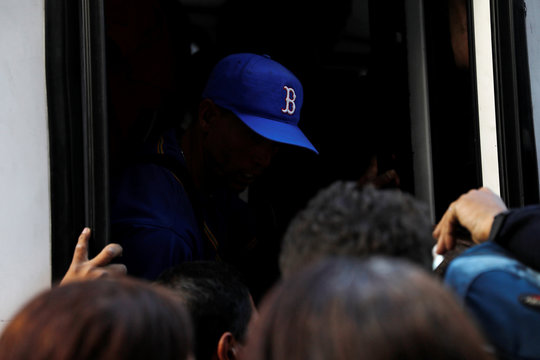 A man wearing a baseball hat is seen inside a bus as people try to board, during a blackout in Caracas