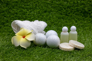 Golf ball with shampoo and soap and towel are on green grass in spa wellness