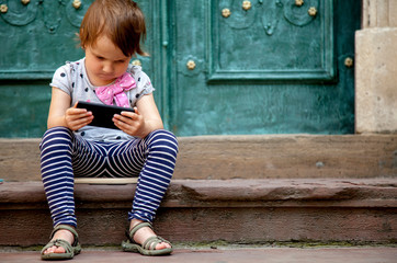 Social networks, friendship, technology and children concept. Portrait of little child girl with phones and headphones.