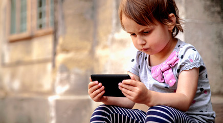 Psychological problems of social media addiction. Little child girl holding smart phone