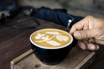 Hand hold and pick a cup of hot coffee cappuccino with cute signature rabbit, flower and leaf latte art pattern in black ceramic cup on rough wooden tray and table.