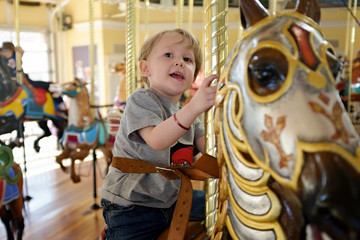Young blond ,toddler aged ,blond haired boy ,riding a brown carousel horse on a merry go round