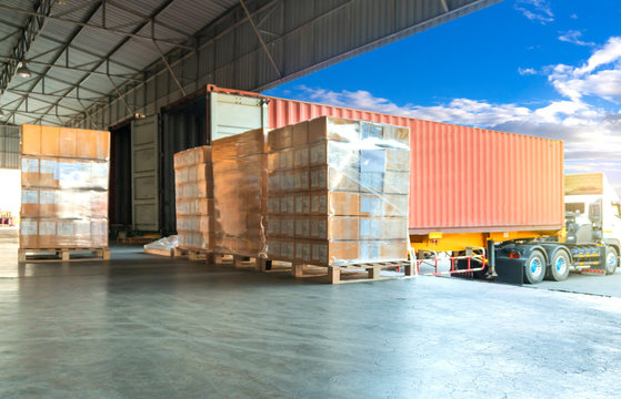 Cargo freight, Shipment, Delivery service. Logistics and transportation. Warehouse dock load pallet goods into shipping container truck. Stacked package boxes on pallets waiting to load into a truck.