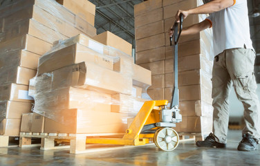 Young man worker is working with hand pallet truck, stack of cardboard boxes shipment at warehouse factory.
