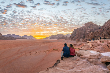 A young couple is watching at sunrise over wadi rum desert in Jordan