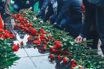 People lay flowers at the Lenin monument on the square
