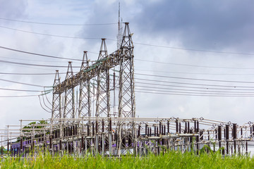 high voltage electric power substation with cloudy dark sky background