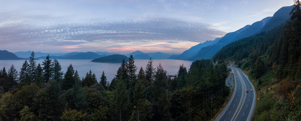Wall Mural - Aerial panoramic view of the scenic highway surounded by the Beautiful Canadian Mountain Landscape during a summer sunrise. Taken in Sunset Beach, North of Vancouver, British Columbia, Canada.
