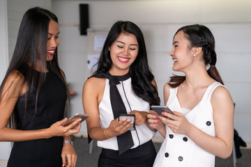 Three women friends having conversation while looking at mobile phone in their hands. Concept of social media, gossip news and online shopping.
