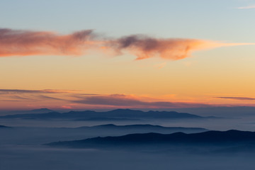 Beautifully colored sky at dusk, with mountains layers and mist between them