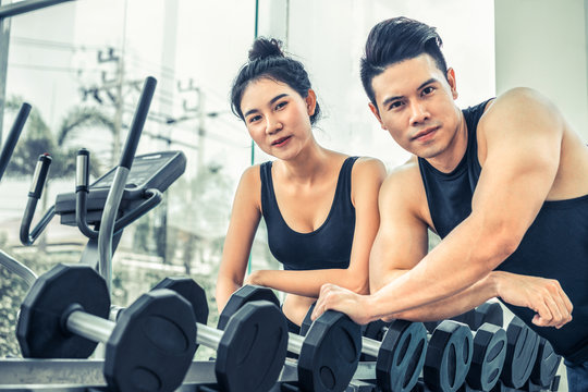 Healthy man and woman doing weight training in gym fitness center. Bodybuilding concept.