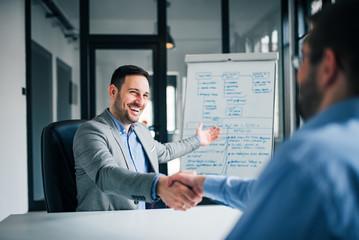 Smiling millennial businessman handshaking coworker, celebrating successful teamwork.