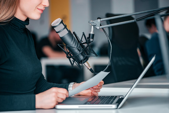 Young woman recording a podcast in a studio, close-up.
