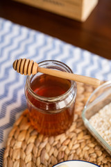 Honey jar with wooden honey dipper on top of it