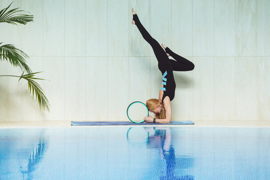 Professional yoga woman doing yoga and pilates with yoga wheel or ring near swimming pool at fitness gym.