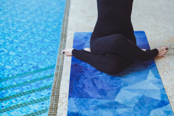 Close-up and details of the yoga legs on cow pose of a young woman, practicing yoga on blue mat