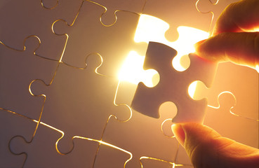 Young businessman trying to put back missing jigsaw puzzle piece with light golden glow effect . Business strategy concept .
