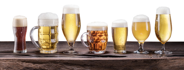 Wall Mural - Beer assortment. Cold different glasses of beer on the wooden table at the white background.