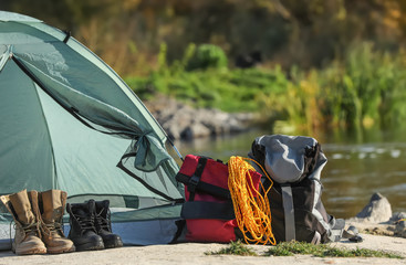 Set of equipment near camping tent outdoors