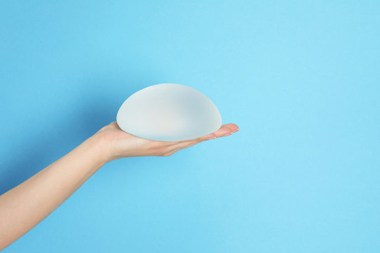Woman holding silicone implant for breast augmentation on color background, space for text. Cosmetic surgery