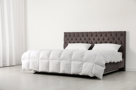 Comfortable bed with new mattress near wall in room. Healthy sleep